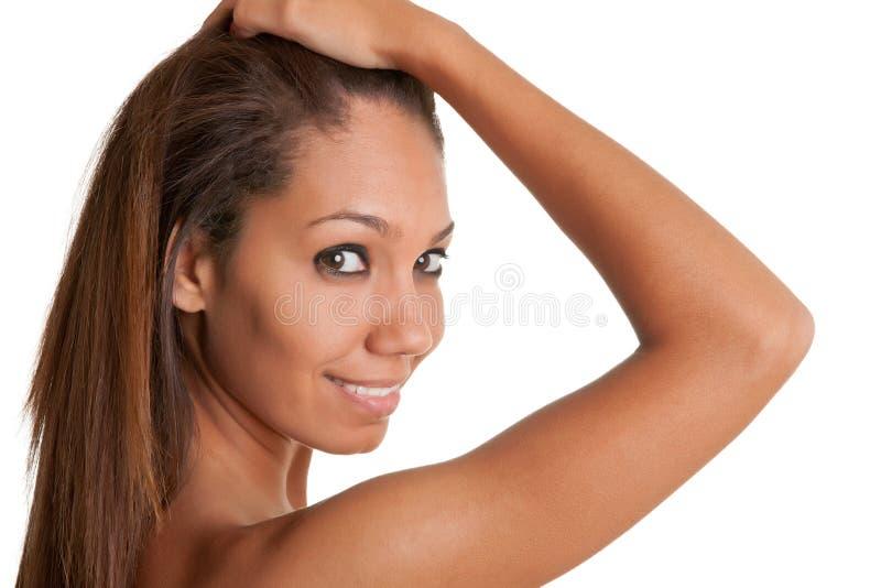 Mulher africana bonita que guarda seus cabelo e sorriso foto de stock