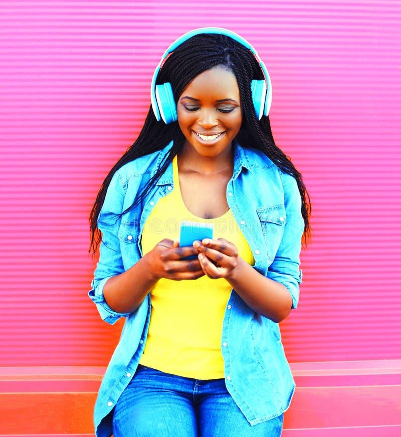 A mulher africana com fones de ouvido escuta a música sobre o rosa imagens de stock