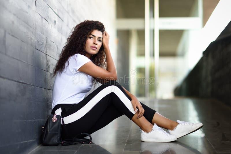 Mulher africana com o penteado encaracolado preto que senta-se no assoalho urbano imagens de stock royalty free