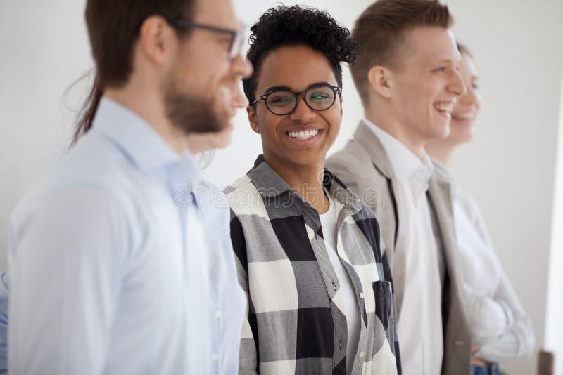 Mulher africana com os colegas que estão de sorriso no escritório fotos de stock royalty free