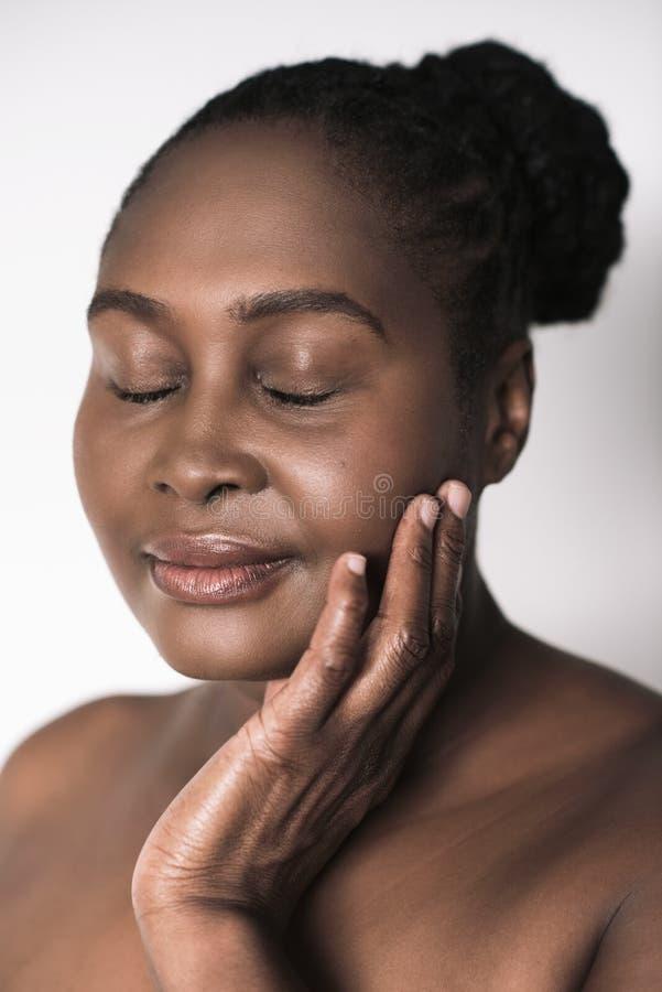 Mulher africana com seus olhos fechados tocando em seu mordente foto de stock