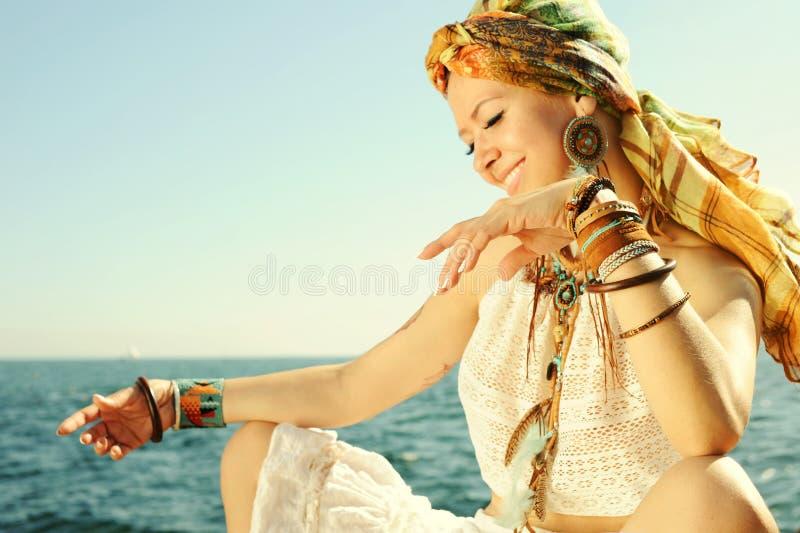 A mulher africana da forma do estilo, vestida na faixa, a camiseta de alças do laço, a colar e os brincos brancos, muitas cobre p fotos de stock