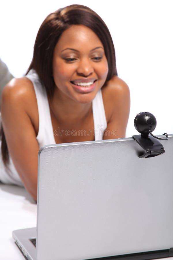 Mulher africana de Amercian que usa a câmara web do portátil imagens de stock