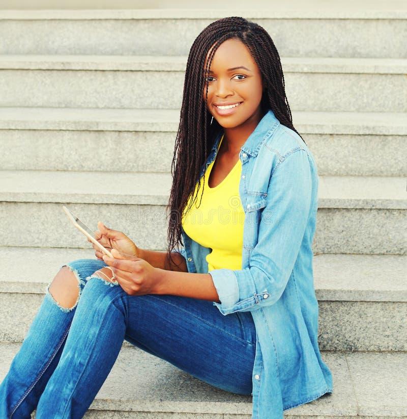 Mulher africana de sorriso dos jovens bonitos que usa o computador do PC da tabuleta na cidade foto de stock