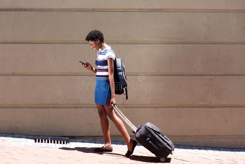 Mulher africana do comprimento completo que anda fora com mala de viagem e telefone celular fotografia de stock royalty free