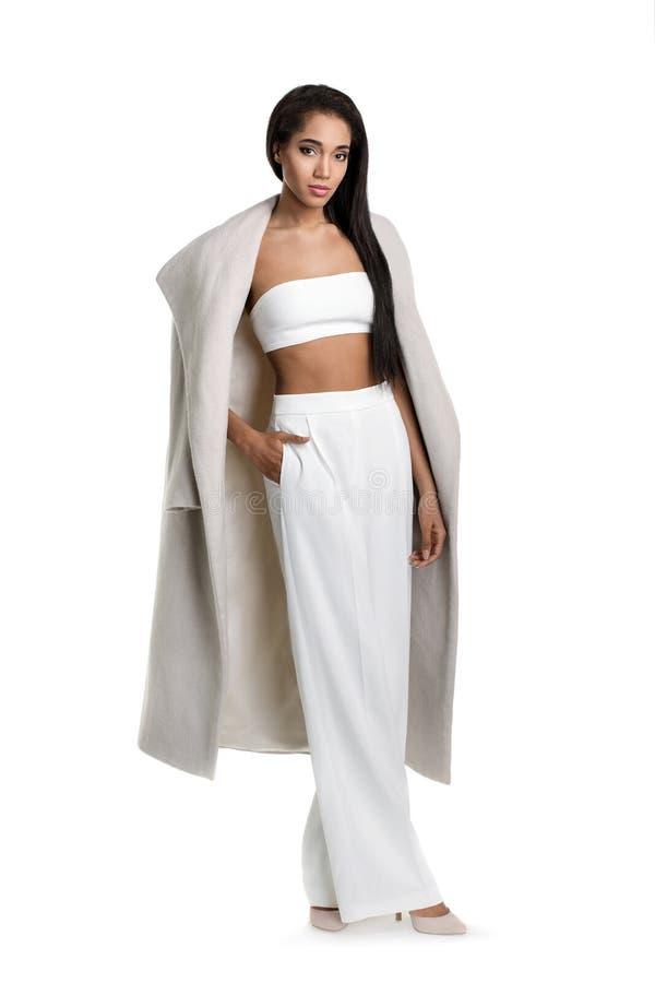 Mulher africana elegante com a roupa branca do cabelo longo que está no empurrão claro do fundo suas mãos em uns bolsos e fotografia de stock