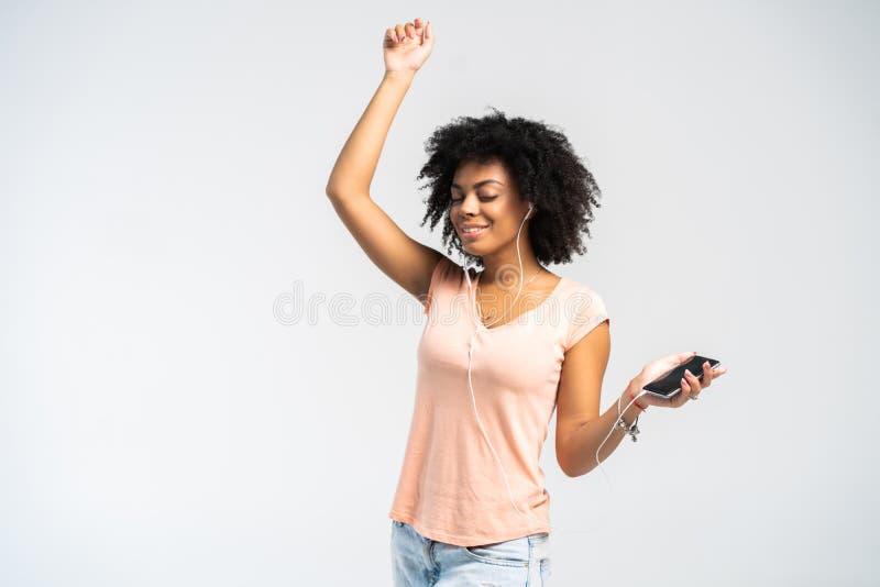 Mulher africana feliz com a roupa afro e ocasional que dança à música está escutando de seu telefone imagem de stock royalty free