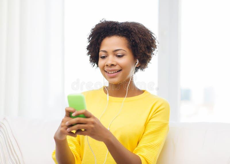 Mulher africana feliz com smartphone e fones de ouvido foto de stock royalty free