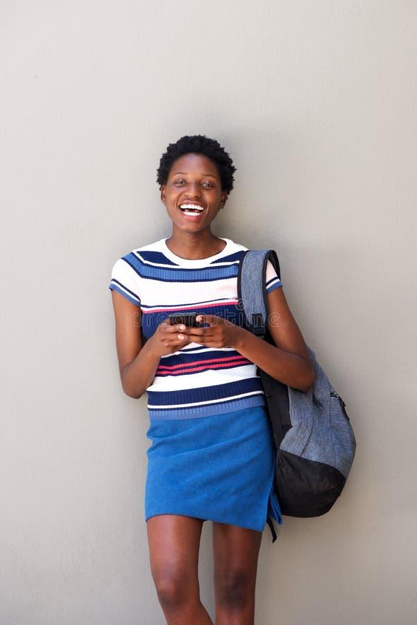 Mulher africana feliz com telefone celular e riso no fundo cinzento foto de stock