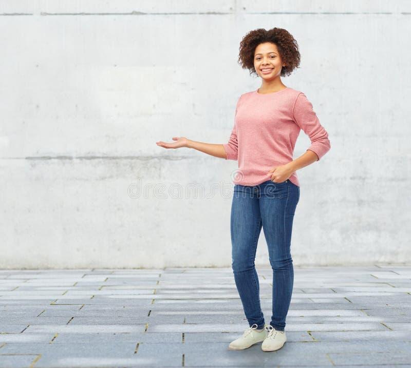 Mulher africana feliz que mantém algo imaginário fotos de stock royalty free