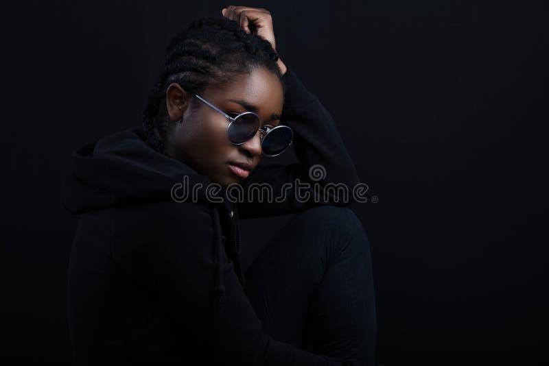 Mulher africana fresca que senta-se com a pele escura que veste ?culos de sol redondos imagem de stock
