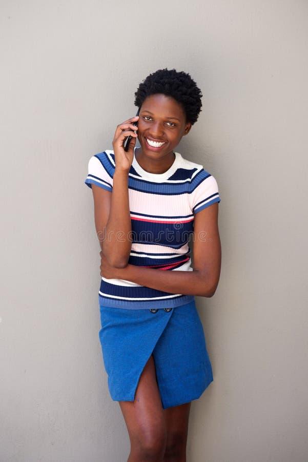 Mulher africana nova à moda que fala no telefone celular contra o fundo cinzento foto de stock royalty free