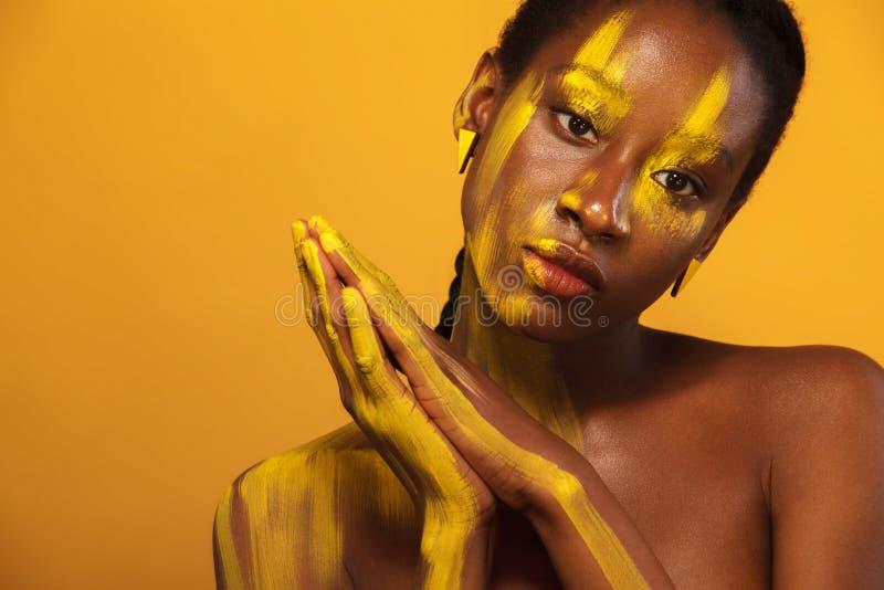 Mulher africana nova alegre com composição amarela da mola em seus olhos Modelo fêmea contra o fundo amarelo do verão imagens de stock royalty free