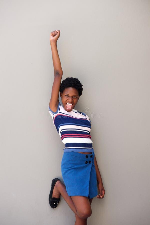 A mulher africana nova alegre que ri com braço aumentou contra o fundo cinzento foto de stock royalty free
