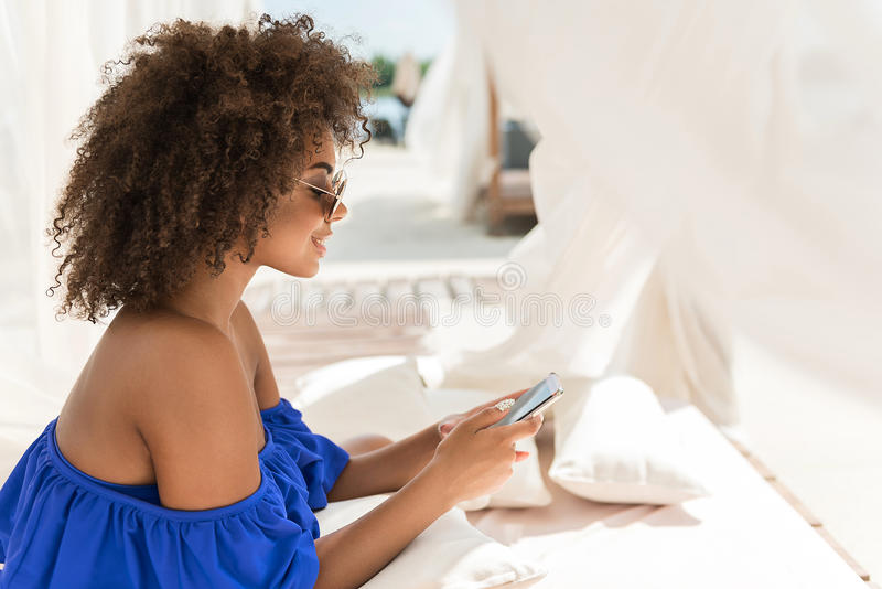 Mulher africana nova animador que texting através do dispositivo na costa do rio imagens de stock royalty free