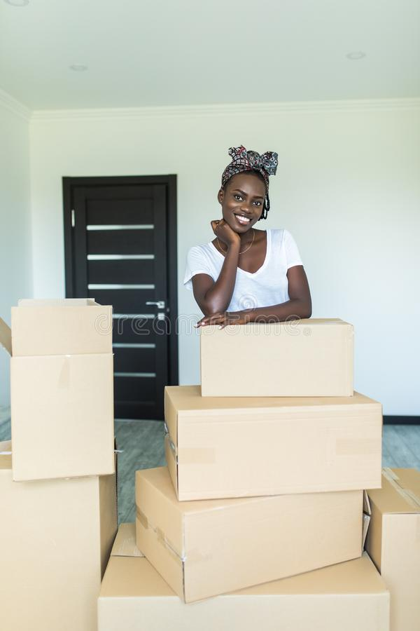 A mulher africana nova atrativa está movendo-se, estando entre caixas de cartão, olhando a câmera e o sorriso fotos de stock