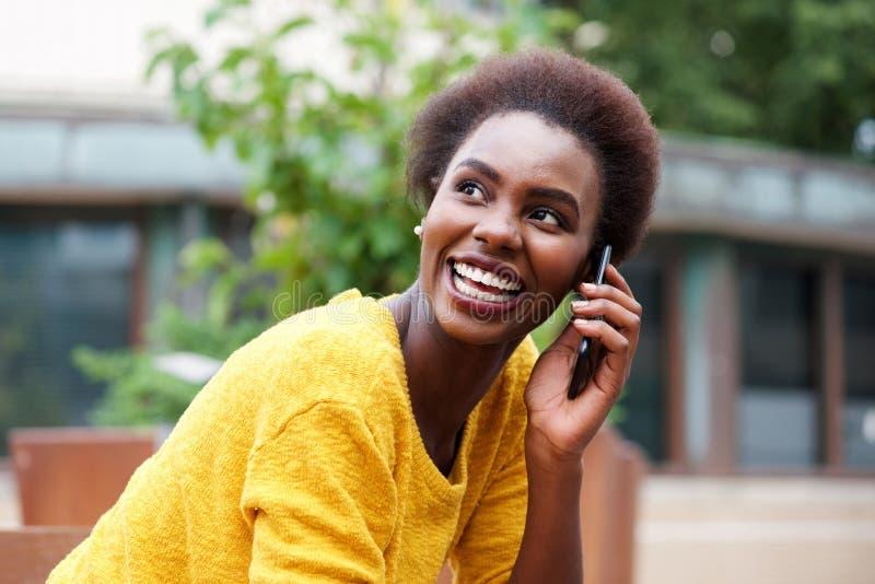 Mulher africana nova bonita que fala no telefone celular fora fotos de stock