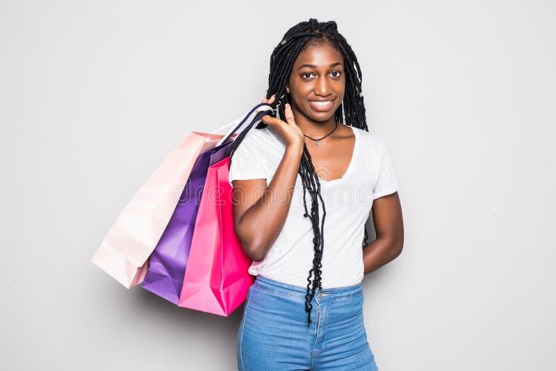 Mulher africana nova com fundo branco isolado sacos de compras imagem de stock royalty free
