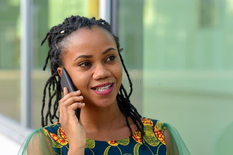 Mulher africana nova consideravelmente na moda em seu móbil foto de stock
