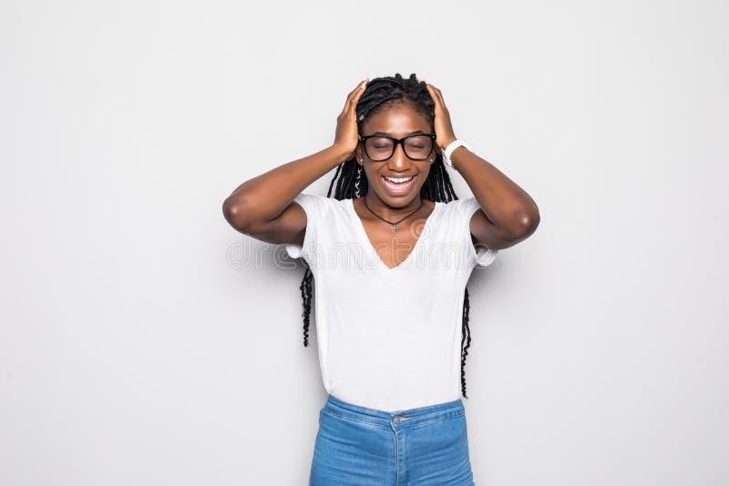 Mulher africana nova de pele escura no t-shirt sleeved longo bege que olha de sobrancelhas franzidas, tendo as expressões doloros fotos de stock
