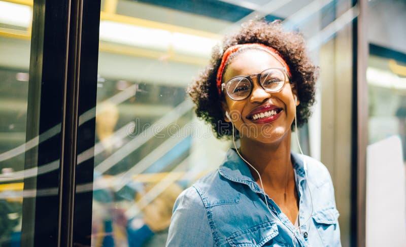 Mulher africana nova de riso que escuta a música no metro imagens de stock