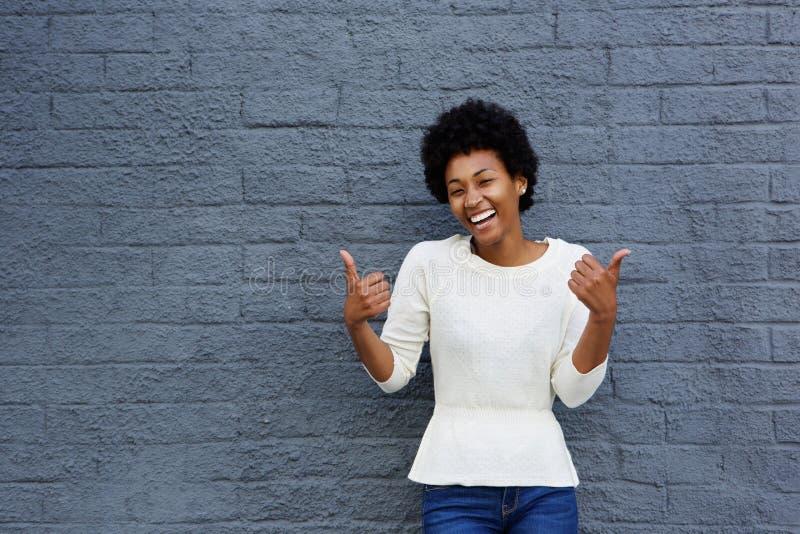 A mulher africana nova de sorriso com polegares levanta o sinal imagem de stock royalty free