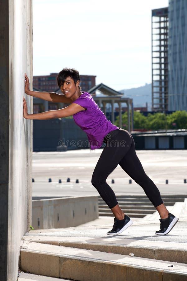 Mulher africana nova do comprimento completo que faz esticando o exercício fora fotos de stock royalty free