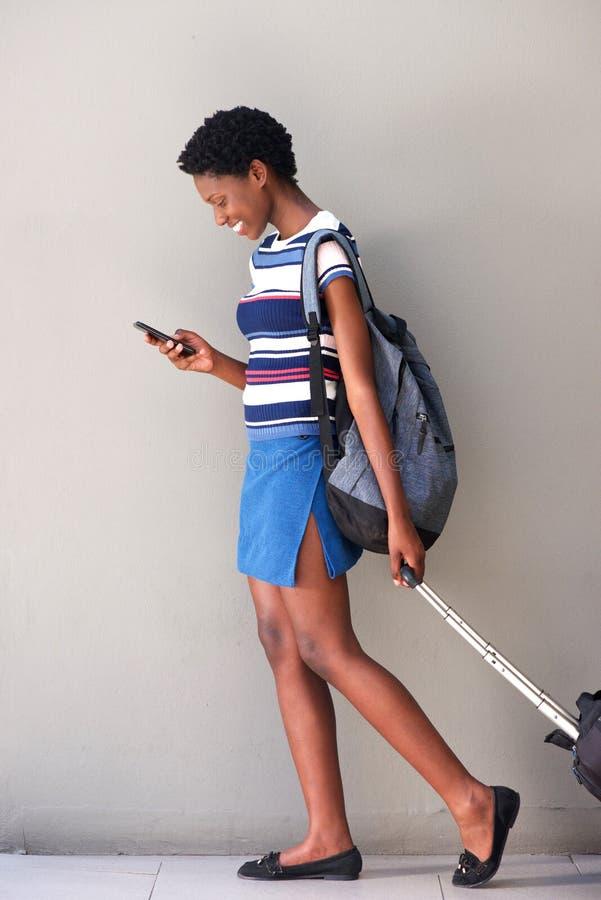 Mulher africana nova do corpo completo que anda com saco do curso e que usa o telefone celular fotos de stock royalty free