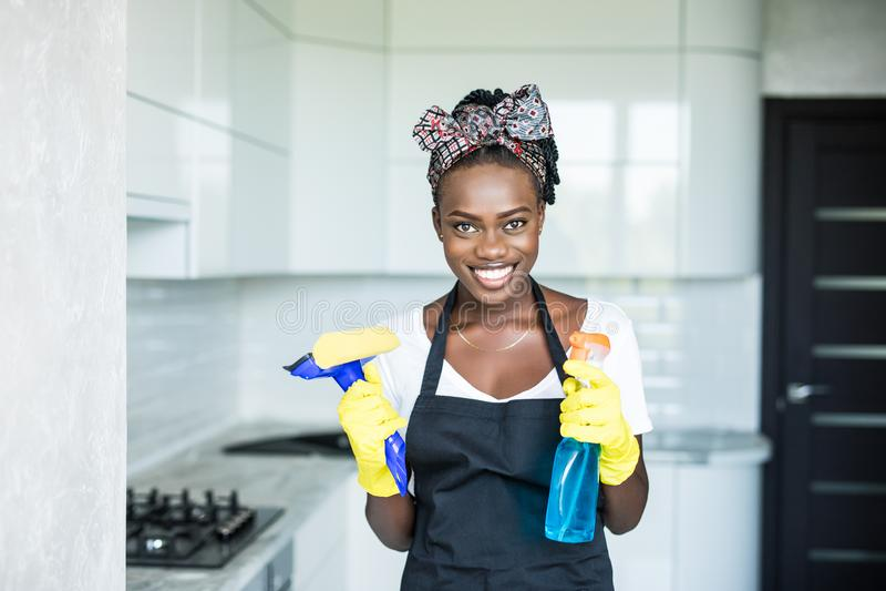 Mulher africana nova do retrato que usa o pulverizador para limpar o vidro de janelas imagens de stock