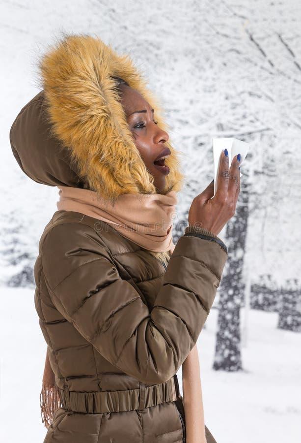 Mulher africana nova doente do retrato do close up com o revestimento encapuçado com pele, fundo do inverno do nariz de sopro imagens de stock royalty free