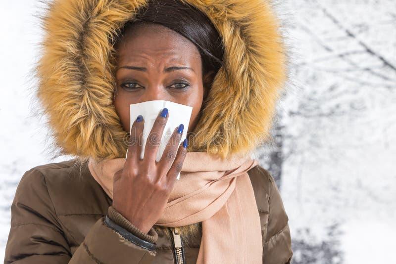 Mulher africana nova doente do retrato do close up com o revestimento encapuçado com pele, fundo do inverno do nariz de sopro foto de stock