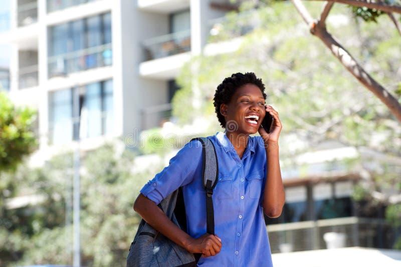 Mulher africana nova feliz que ri com telefone celular fora fotografia de stock royalty free