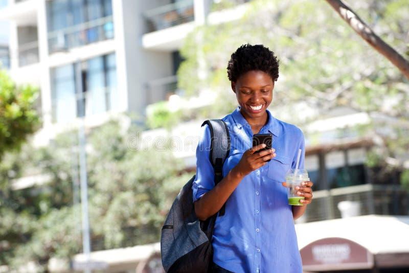 Mulher africana nova fresca que anda fora na cidade usando o telefone celular foto de stock royalty free