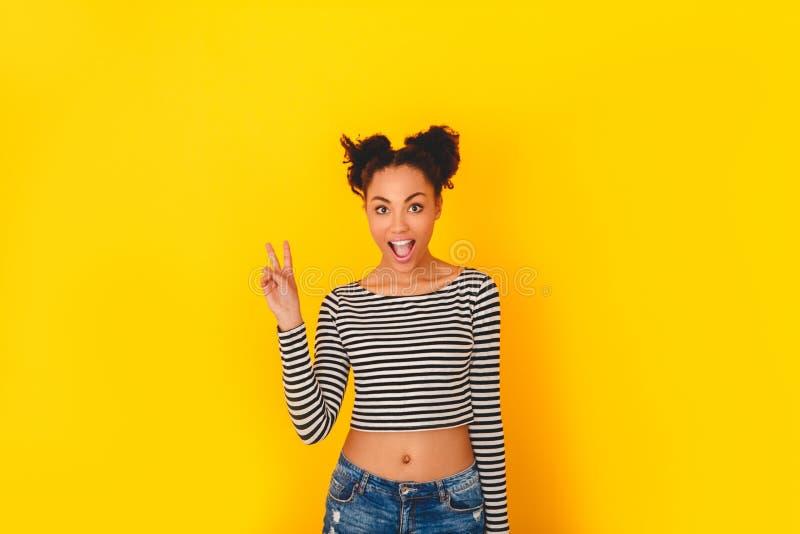 Mulher africana nova isolada no estilo adolescente do estúdio amarelo da parede fresco imagem de stock