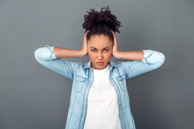 Mulher africana nova isolada no estilo de vida diário ocasional do estúdio cinzento da parede irritado foto de stock