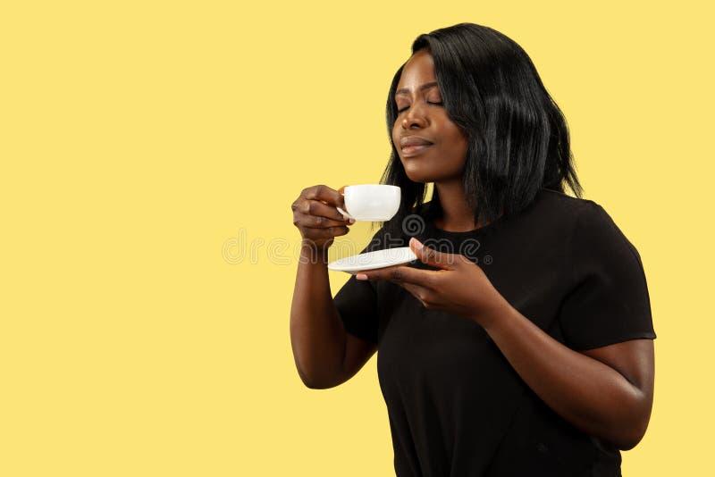 Mulher africana nova isolada no fundo amarelo do estúdio, expressão facial imagens de stock royalty free