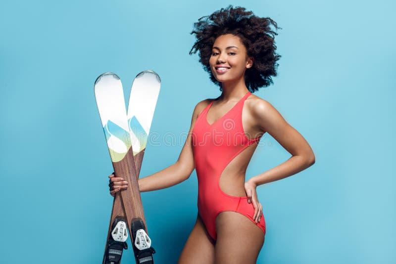 Mulher africana nova no roupa de banho isolado no levantamento azul do esqui do estúdio da parede imagens de stock royalty free