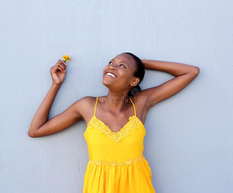 Mulher africana nova no vestido amarelo uma flor imagem de stock