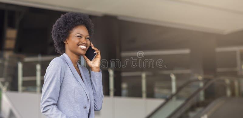 Mulher africana nova que fala no telefone na frente do centro de negócios fotos de stock royalty free