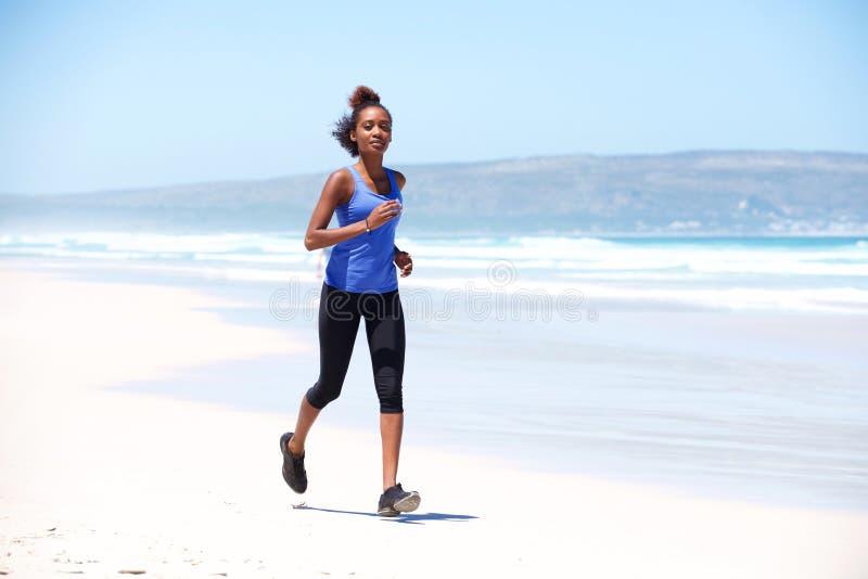 Mulher africana nova que movimenta-se ao longo da costa de mar fotografia de stock