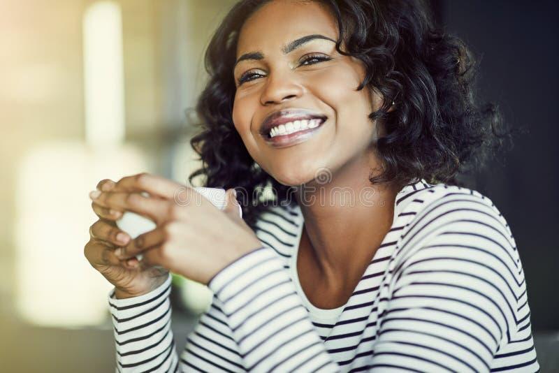 Mulher africana nova que ri ao apreciar o café em um café foto de stock royalty free