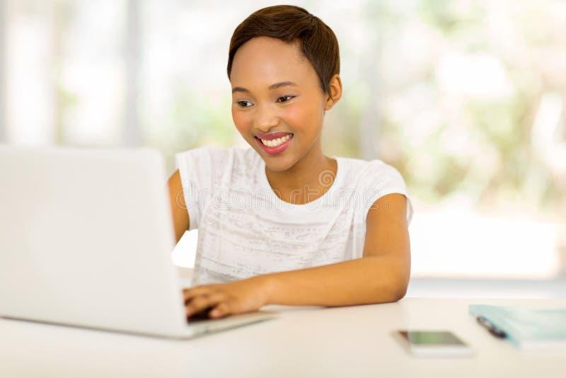 Mulher africana nova que senta-se na frente do portátil fotos de stock royalty free