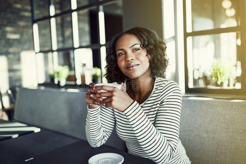 Mulher africana nova que sorri ao apreciar o café em um café imagens de stock royalty free