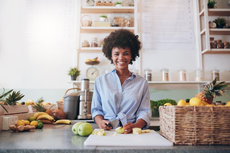 Mulher africana nova que trabalha na barra de suco foto de stock