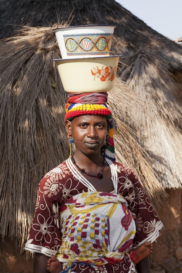 Mulher africana que leva dois pratos em sua cabeça foto de stock royalty free