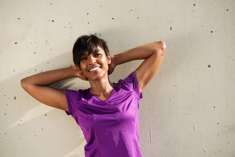 Mulher africana que relaxa contra a parede com mãos atrás da cabeça imagem de stock