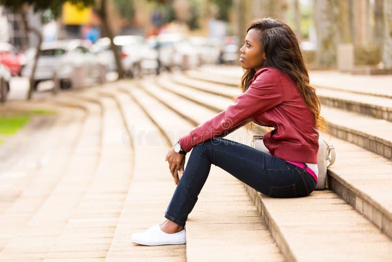 Mulher africana que senta-se fora fotos de stock royalty free