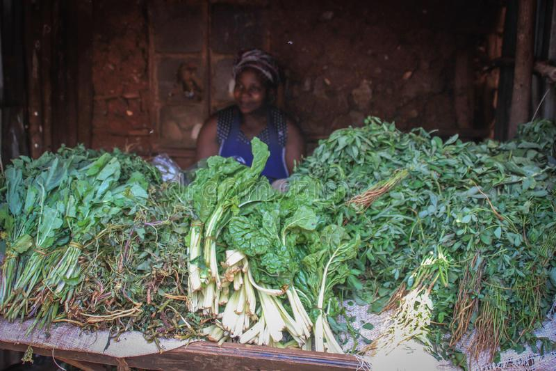Mulher africana que vende verdes no contador em uma das cidades as mais pobres em África imagem de stock royalty free