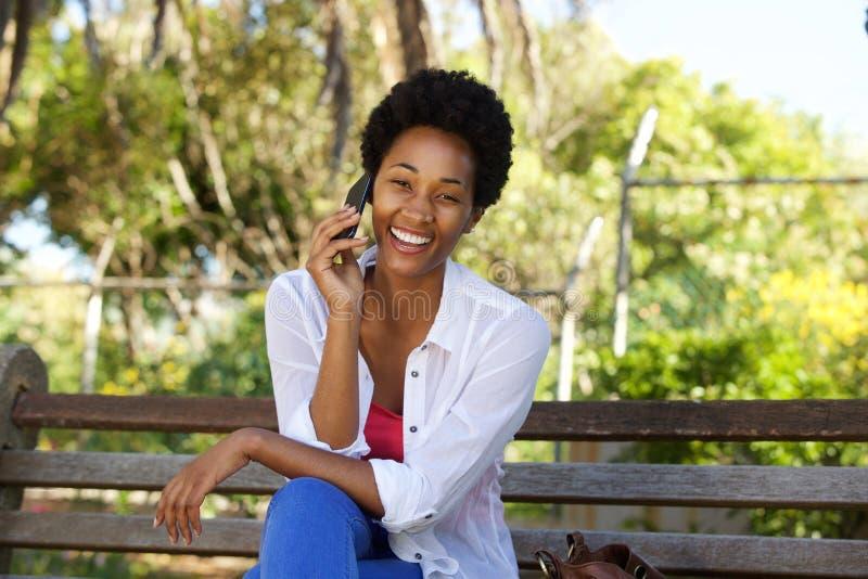 Mulher africana relaxado que senta-se em um banco de parque e que usa o telefone celular foto de stock royalty free