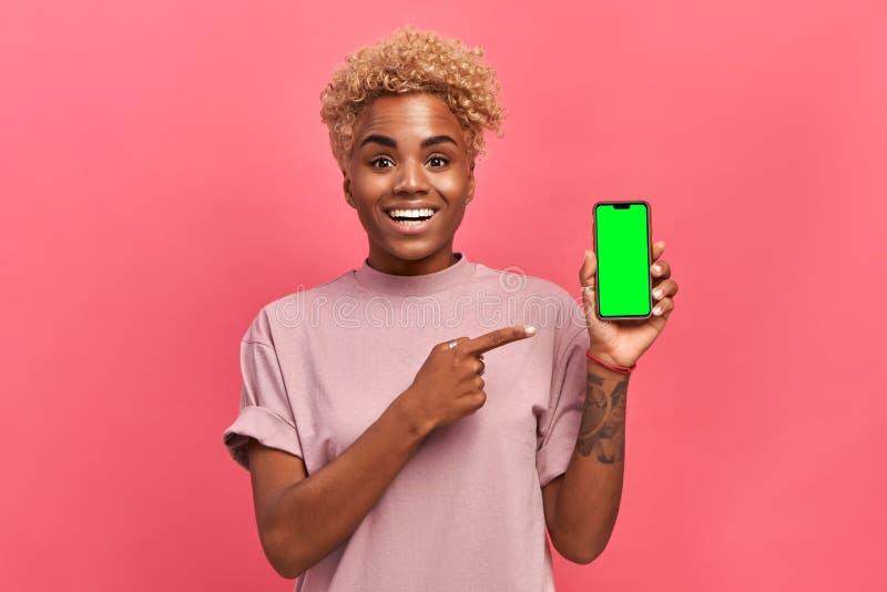 Mulher africana se mostrando no smartphone e apontando com o dedo indicador ao zombar fotografia de stock royalty free